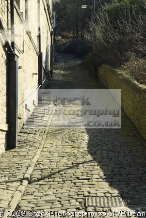 cobbled street going hill old factory buildings unusual british strange wierd uk cobbles road steep hilly climb industrial halifax yorkshire england english great britain united kingdom