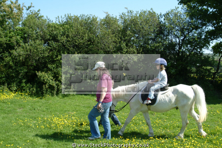 child supervised learning ride horse rural britain countryside rustic pastoral environmental learn cornwall cornish england english angleterre inghilterra inglaterra united kingdom british