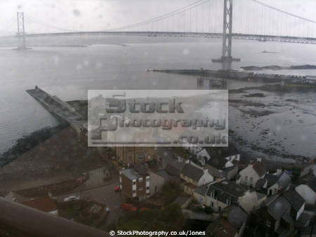 north queensferry wet winter afternoon. taken on-board on board onboard train forth bridge. uk bridges rivers waterways countryside rural environmental oppressive gloomy cloudy rain shower firth road grey rail estuary river fife scotland scottish scotch scots escocia schottland united kingdom british