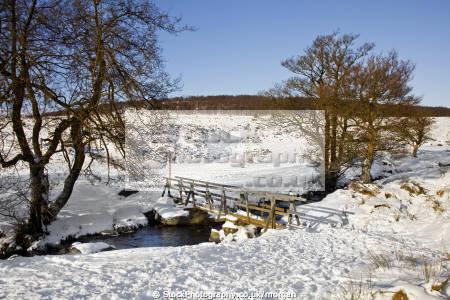 burbage brook winter grindleford derbyshire countryside rural environmental wooden foot bridge snow prints stream trees peak district england english angleterre inghilterra inglaterra united kingdom british