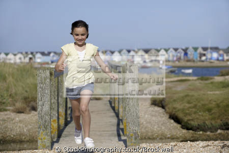 young girl skipping running foot bridge smiling beach huts background summer holiday dorset girls female children kids juveniles infants females feminine womanlike womanly womanish effeminate ladylike child happy childhood exercise fun seaside bournemouth england english angleterre inghilterra inglaterra united kingdom british