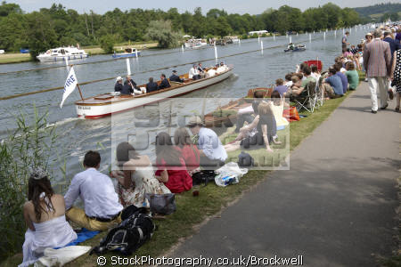 spectators watching rowing race royal henley regatta oxfordshire thames riverside summer.men summer men summermen women sitting river bank sun body language competition berkshire watch club enclosure henley-on-thames henley on thames henleyonthames home counties england english angleterre inghilterra inglaterra united kingdom british