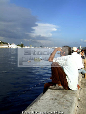 man fishing havana harbour cuba human activities caribbean cuban