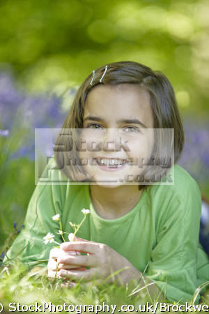 young cute girl lying wood bluebells touching petals spring time forest chilterns buckinghamshire girls female children kids juveniles infants females feminine womanlike womanly womanish effeminate ladylike flowers nature touch smile high wycombe bucks england english angleterre inghilterra inglaterra united kingdom british