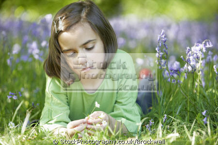 young cute girl lying wood bluebells touching petals spring time forest chilterns buckinghamshire girls female children kids juveniles infants females feminine womanlike womanly womanish effeminate ladylike flowers nature touch high wycombe bucks england english angleterre inghilterra inglaterra united kingdom british