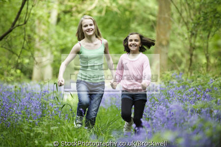 young girls sisters friends running bluebells camera smiling laughing holding hands wood springtime female children kids juveniles infants females feminine womanlike womanly womanish effeminate ladylike flowers nature forest fun childhood high wycombe buckinghamshire bucks england english angleterre inghilterra inglaterra united kingdom british