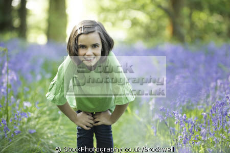 young cute pretty girl smiling camera wood forest wild flowers bluebells season spring time buckinghamshire girls female children kids juveniles infants females feminine womanlike womanly womanish effeminate ladylike childhood high wycombe bucks england english angleterre inghilterra inglaterra united kingdom british