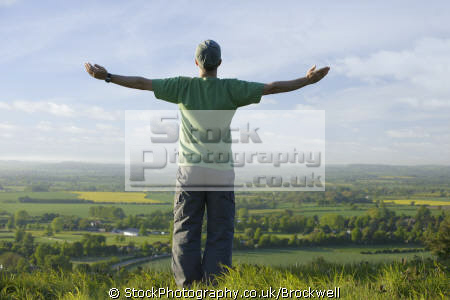 man standing landscape arms stretched looking horizon distance country fields buckinghamshire chilterns body language environment high wycombe bucks england english angleterre inghilterra inglaterra united kingdom british