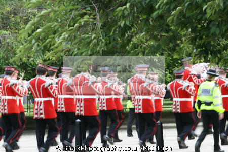 loyal orange lodge parade. band photo red tunics black trousers. tree lined entering park march procession gathering glasgow central scotland scottish scotch scots escocia schottland united kingdom british