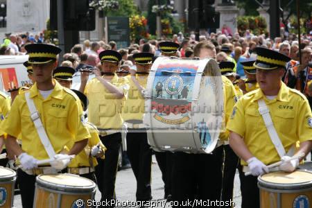 loyal orange lodge parade. band march wearing yellow shirts dark trousers. bass drummer drummers procession gathering glasgow central scotland scottish scotch scots escocia schottland united kingdom british