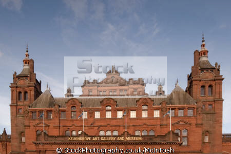 red sandstone building flying scottish flags blue sky. uk art galleries british architecture architectural buildings kelvingrove glasgow central scotland scotch scots escocia schottland united kingdom