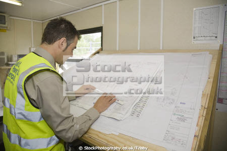 engineer inspecting elecctrical plans drawing board site office building construction uk business commerce cambridge cambridgeshire electrical emcore england genome campus norfolk engineering home counties english angleterre inghilterra inglaterra united kingdom british