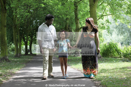 mixed race family walking path laughing together park setting multicultural ethnic minority summer unity love togetherness mother father daughter black white happiness happy