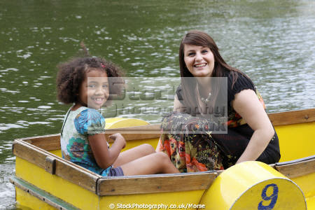 young mixed race girl white mother sitting together yellow boat boating pond multicultural ethnic minority summer smile happiness happy daughter water