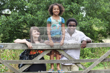 mixed race family leaning gate countryside multicultural ethnic minority summer smile happiness happy father daughter mother black white