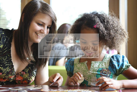 young mixed race girl sitting table playing game white mother multicultural ethnic minority summer smile child children family daughter play fun amusement