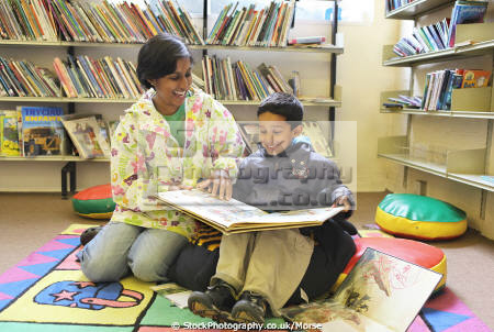 young asian boy sitting mother reading book together library laughing multicultural ethnic minority concentration child children education learning asians books libraries son happy