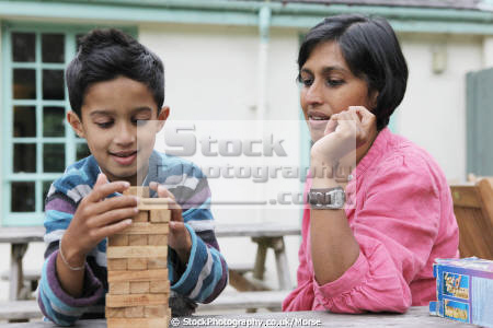 asian boy sitting outside mother playing game jengo multicultural ethnic minority asians amusement concentration child children son family games
