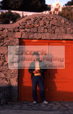 hunky guy standing orange door men adult males masculine manlike manly manful virile mannish people persons waiting benny mykonos greek island dodcanese islands greece europe european