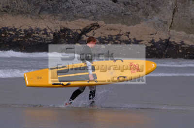 lifeguard carrying surfboard rnli coastguard lifeboat rescue uk emergency services safety baywatch newquay cornish cornwall england english angleterre inghilterra inglaterra united kingdom british